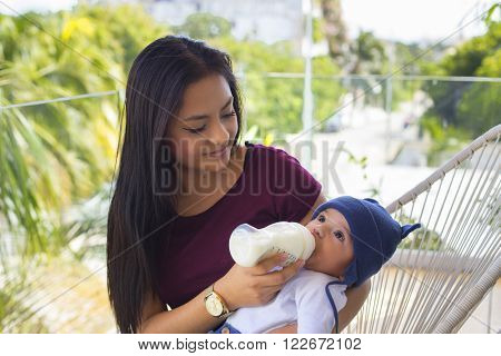 Beautiful mexican woman feeds her baby