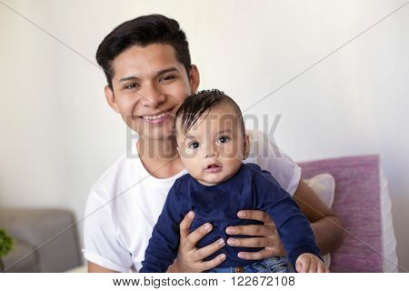 Young mexican father takes care of his six month baby boy