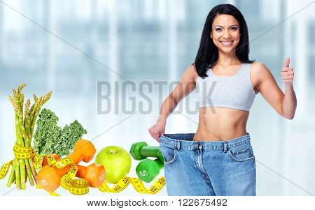 Slimming woman wearing big pants over blue background.