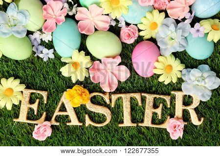 Colorful Easter eggs on grass with flowers background