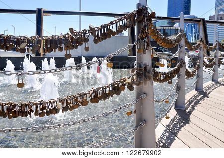 Draped fence of engraved golden love locks on chained fence of bridge outside the Bell Tower in Perth, Western Australia with a water fountain in the background.