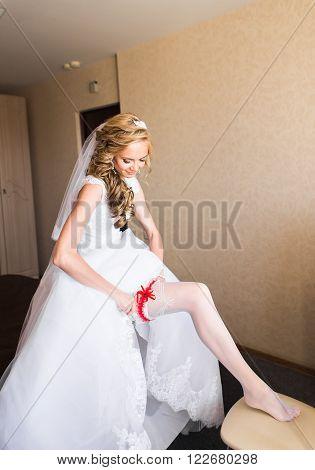 bride dresses garter on the leg. Picture of beautiful female barefoot legs in wedding dress. Bride dresses stockings on feet. Bride putting a wedding garter on her leg