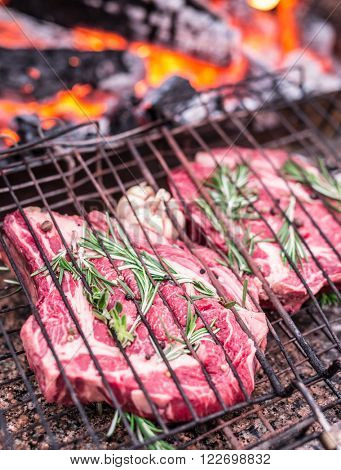 Rib steaks and grill with burning fire behind them.