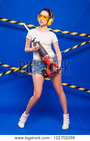 Sexy Brunette Builder On A Blue Background With An Electric Tool In The Hands Of