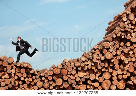 Crisis - business man running   down  from the top of large pile of logs