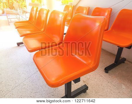 The empty orange colour chairs in row on the floor with sunlight.