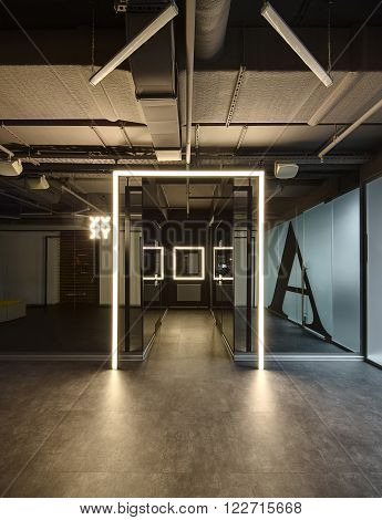 Loft style interior. Mirrored walls with reflected parts of the room in it. Between the walls there is a corridor with doors on each side and a luminous window frame at the end. Start of corridor allocated by luminous frame. There is a luminous pointer on