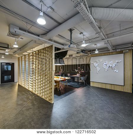 Interior in a loft style. There are tables, chairs and a board with stickers. Above them hang large lamp with artificial leaves. Laptop, notebooks, handlers with pens are on the table. On the right there is a wall with world map on it. On the left there i
