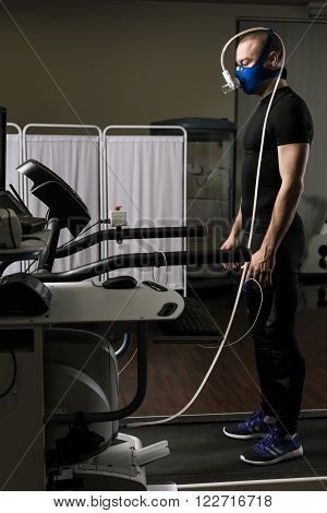 Young man during cardiac stress test standing with mask on treadmill