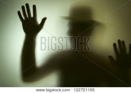 Shadowy figure behind glass
