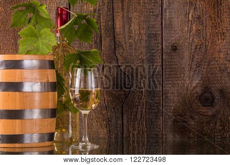 Glass of wine with barrel white bottle behind grapeleaves and dark wooden background