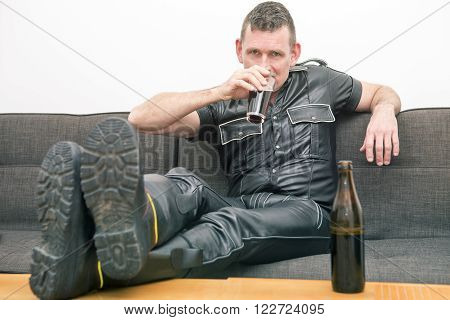 man wearing black fetish leather clothessitting on couch and drinking a beer