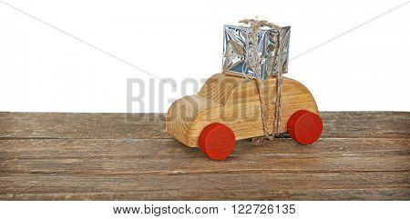 Wooden toy car with gift box on a table over white background
