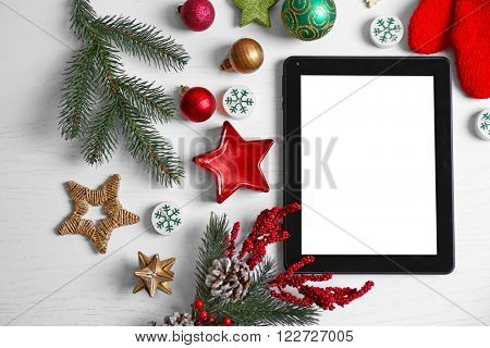 Tablet and Christmas decor on white wooden background
