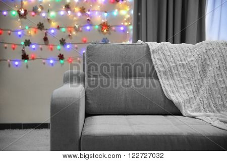 Grey couch with plaid on Christmas lights background