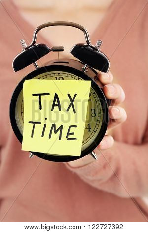 Woman in brown sweater holding alarm with tax time inscription, close up