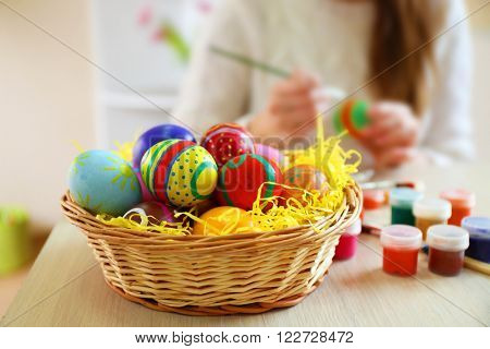Female hands painting Easter eggs at table indoors