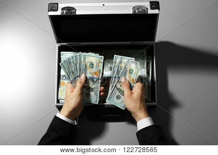 Businessman counting money on grey background