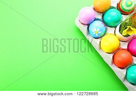 Easter eggs with yellow flower in tray on green background