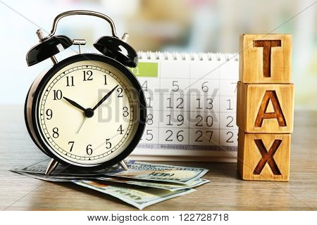 Tax time and alarm clock with dollars and calendar