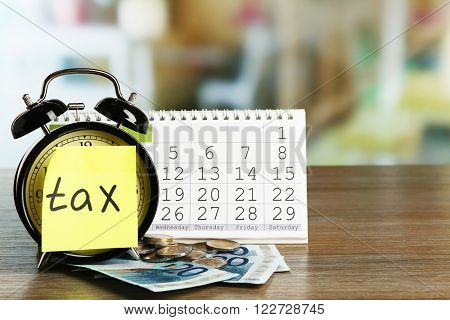 Tax time on alarm clock with euro, coins and calendar