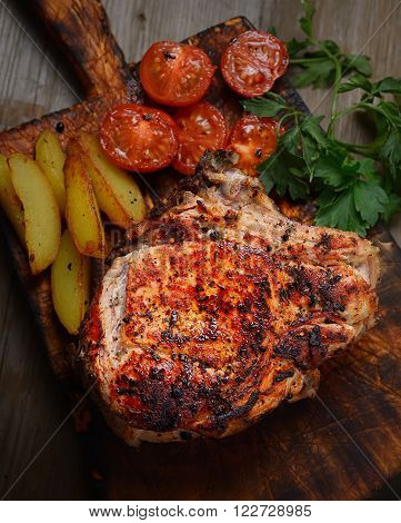 juicy steak with potatoes, tomatoes and herbs on a cutting board