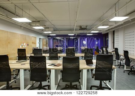 Hall in a loft style. There are many wooden tables with gray legs and black chairs. On the tables there is laptop, tablet, phone, bag, pens, papers and notebooks. Left wall is white with wooden panels with stickers on it. There is a glass door at end of t