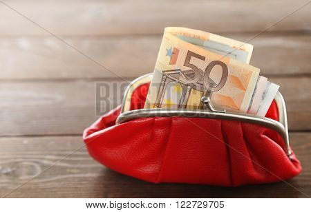 Purse with euros inside on wooden background