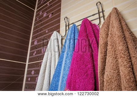 Clean Colored Towels Hanging On The Rack In The Bathroom.