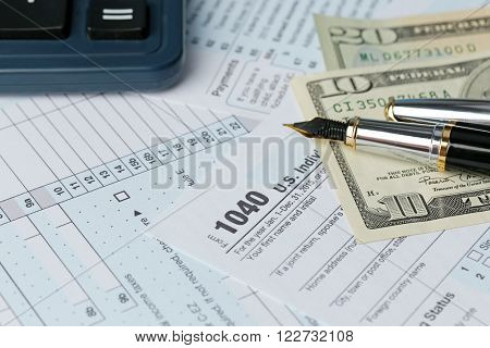 1040 Individual Income Tax Return Form for 2015 year with a pen to fill in and dollar bills, close up