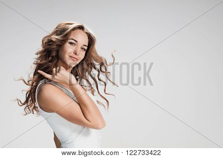 The young woman's portrait with happy emotions on gray background