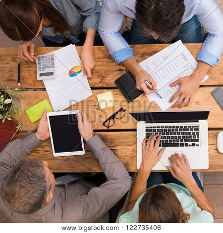 Businesspeople analyzing schemes and diagrams. Successful business people working with documents at the office. Group of businesspeople working together in office.
