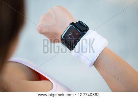 Female runner checking pulse on her smart watch