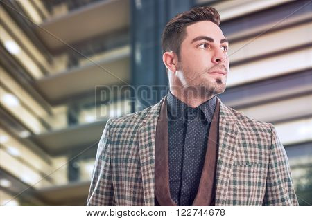 Confident and successful business man with company building as background