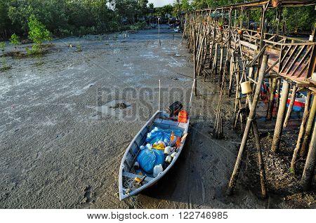 fishing sampan stranded near to wooden pier in Asia