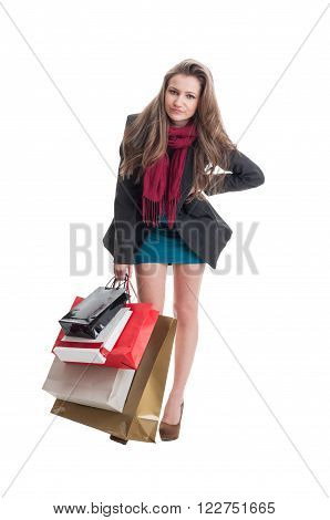 Dissapointed shopping woman carrying many heavy bags
