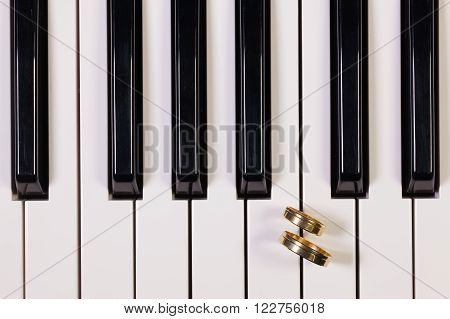 Detail of piano keyboard and wedding rings