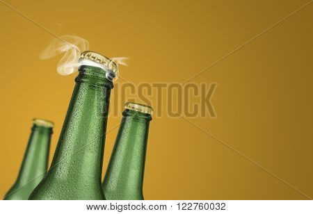 Horizontal photo of three green cold beer bottles with water drops and golden cap open on yellow background