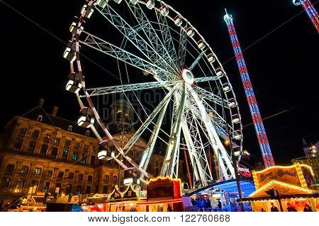 AMSTERDAM, NETHERLANDS - APRIL 27: Attractions on Dam Square at night during King's Day on April 27, 2015 in Amsterdam. King's Day is the largest open-air festivity in Amsterdam.