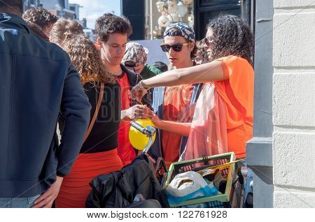 AMSTERDAM-APRIL 27: Unidentified woman sells laughing gas to young people during King's Day on April 27, 2015 in Amsterdam the Netherlands.