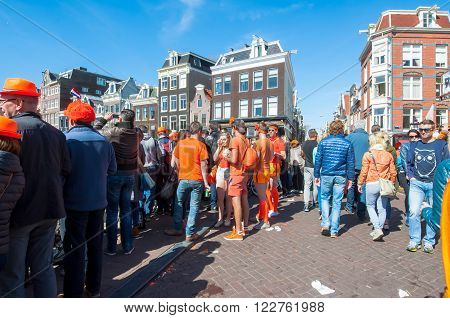AMSTERDAM-APRIL 27: Locals and tourists celebrate King's Day on the bridge on Singel canal on April 272015 the Netherlands. King's Day is the largest open-air festivity in Amsterdam.