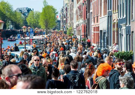 AMSTERDAM-APRIL 27: Locals and tourists celebrate King's Day along the Singel canal on April 272015 the Netherlands. King's Day is the largest open-air festivity in Amsterdam.
