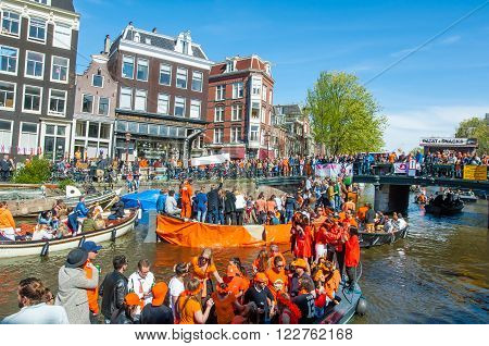 AMSTERDAM-APRIL 27: Locals and tourists on the boats participate in celebrating King's Day on April 272015 the Netherlands. King's Day is the largest open-air festivity in Amsterdam.