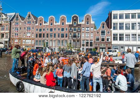 AMSTERDAM-APRIL 27: People on the boats participate in celebrating King's Day through Singel canal on April 272015 the Netherlands. King's Day is the largest open-air festivity in Amsterdam.