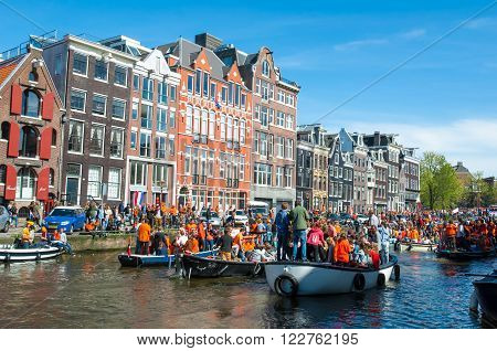 AMSTERDAM-APRIL 27: People on the boats participate in celebrating King's Day through Amsterdam canal on April 272015 the Netherlands. King's Day is the largest open-air festivity in Amsterdam.
