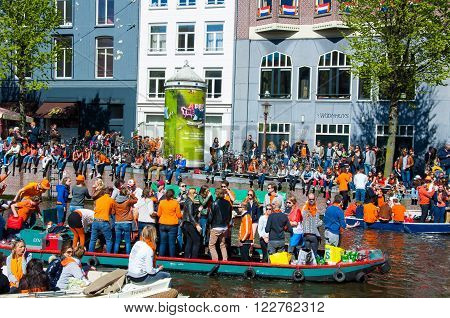 AMSTERDAM-APRIL 27: Party Boat on Singel canal with crowd of people on the street during King's Day on April 272015. King's Day is the largest open-air festivity in Amsterdam.