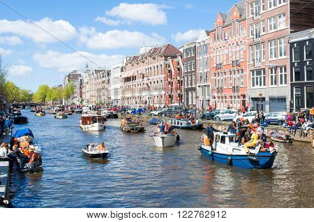 AMSTERDAM-APRIL 27: Celebrating King's Day along the Singel canal on April 272015. King's Day is the biggest festival celebrating the birth of Dutch royalty.