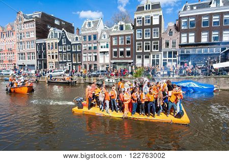AMSTERDAM-APRIL 27: Happy People in orange celebrate King's Day along the Singel canal on the raft on April 272015. King's Day is the biggest festival celebrating the birth of Dutch royalty.