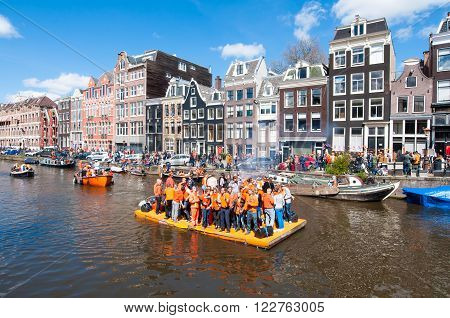 AMSTERDAM-APRIL 27: Happy People celebrate King's Day along the Singel canal on the orange raft on April 272015. King's Day is the biggest festival celebrating the birth of Dutch royalty.