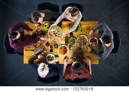 Top view creative photo of friends sitting at wooden vintage table. Friends of six having dinner. They with plates full of delicious meal and glasses with drinks